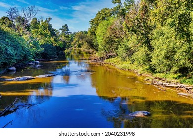 Raleigh, North Carolina USA-09 12 2021: The Neuse River in Summer with Shallow Water Exposing Rocks.