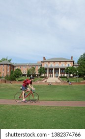 RALEIGH,NC/USA - 4-25-2019: A student rides a bike across the campus of North Carolina State University in Raleigh