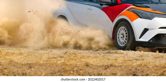 Rally race car drifting in curve on dirt track.