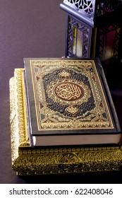 Ramadan Background - The Holy Quraan in golden box with Ramadan Lantern on black background
