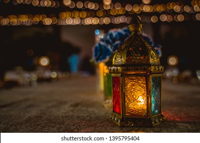 Ramadan colorful lantern on a table with flowers and fairy lights in the background