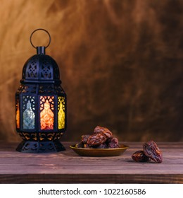 Ramadan concept. Dates close-up in the foreground. On the distant plan a blurry Ramadan Lantern on a wooden table. Textured yellow wall background. Space for text on the right. Square 1:1 frame.