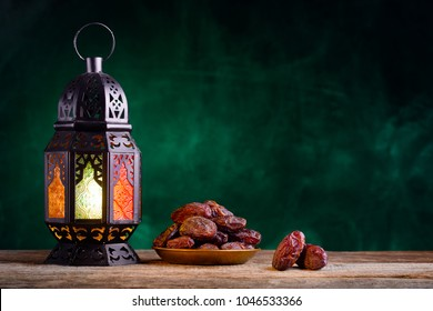 Ramadan concept. Dates close-up in the foreground. Ramadan Lantern on a wooden table. Textured green wall background. Space for text on the right.