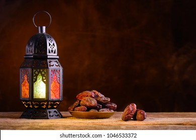 Ramadan concept. Dates close-up in the foreground. Ramadan Lantern on a wooden table. Textured yellow wall background. Space for text on the right.