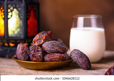 Ramadan concept. Dates close-up in the foreground. Ramadan Lantern and glass of milk on a wooden table. Dark brown wall background. Selective focus, low depth of field, bokeh