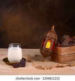 Ramadan concept. Dates close-up in the foreground. Ramadan Lantern and glass of milk on a wooden table. Dark brown wall background. Space for text on the left. Square 1:1 frame.
