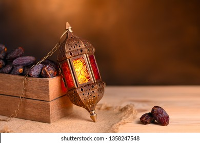 Ramadan concept. Dates close-up in the foreground. Box with dates and ramadan lantern on a wooden table. Blurred dark textured wall background. Plase for text on the right