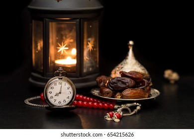 Ramadan concept with dates, pocket watch, rosary and lantern in darkness