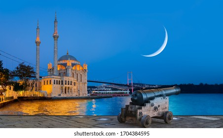 Ramadan Concept - Ortakoy mosque and Bosphorus bridge with crescent and cannon at twilight blue hour - Istanbul, Turkey