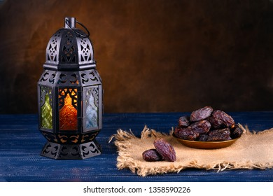 Ramadan concept. Stillife with a Ramadan Lantern and plate with dates. Dark blue wooden table. Blurred dark textured wall background. Plase for text on the right.