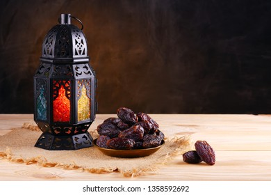 Ramadan concept. Stillife with a Ramadan Lantern and plate with dates. Wooden table. Blurred dark textured wall background. Plase for text on the right.