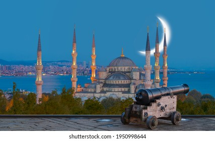 Ramadan Concept - Sultan Ahmet Mosque and Bosphorus with crescent moon, Black a cannon in the foreground at twilight blue hour - Istanbul, Turkey