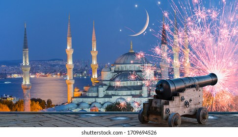 Ramadan Concept - Sultanahmet mosque and Bosphorus with crescent moon and cannon at twilight blue hour - Istanbul, Turkey