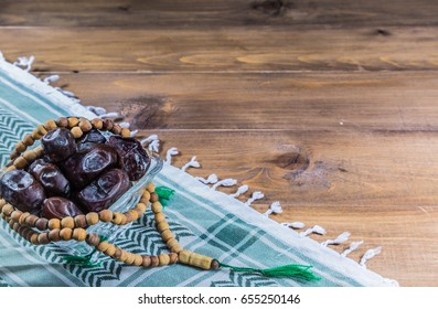 Ramadan festival and wooden rosary in dark wooden table isolated on black background.Dates fruit. Pile of dried date fruits in glass on dark wooden.