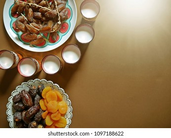 Ramadan food background concept beginning the iftar meal with dried apricots, dates, milk flat lay on brown background with evening sunlight. (top view, space for text, article layout design)