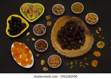 Ramadan Food Background with copy space - Top View of a black wooden table with different kinds of Arabian food (dried fruits and nuts ) ready for iftar (breakfast) in Ramadan