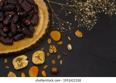 Ramadan Food Background with copy space - Top View of a black wooden table with different kinds of Arabian food ( dried dates and fruits ) ready for iftar (breakfast) in Ramadan