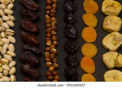 Ramadan Food Background - Top View of a black wooden table with different kinds of Arabian food (dried fruits and nuts ) ready for iftar (breakfast) in Ramadan
