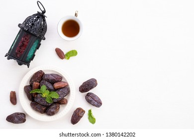 Ramadan food and drinks concept. Ramadan Lantern with tea, dates fruit, grape and Mint leaves on a white wooden table background. Top view, Flat lay.