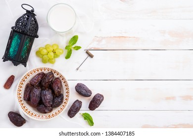 Ramadan food and drinks concept. Ramadan Lantern with Milk, dates fruit, grape and Mint leaves on a white wooden table background. Top view, Flat lay.