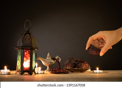 Ramadan food and drinks concept. Woman hand reaches out to a plate with date with Ramadan Lantern with arabian lamp, wood rosary, tea, dates fruit and lighting on a wooden table on dark background.