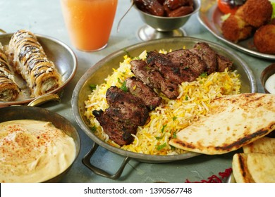 Ramadan food feast background  /Iftar party concept -Lamb Kababs,rice, Hummus,Lavash bread dates and Baklava, selective focus