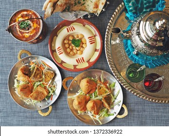 Ramadan food preparation for iftar meal during the holy month : Hummus with canned chickpeas, Halal chicken samosas, Dal Makhani, Naan bread, tea pot and glass flat lay on the dining table. (top view)