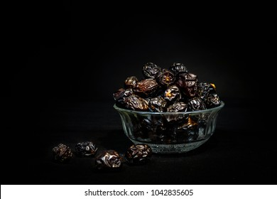 Ramadan Greetings- Eid Mubarak- dates fruits on black background with dramatic light.