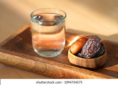 Ramadan iftar food, delicious date fruits and water on wooden plate.