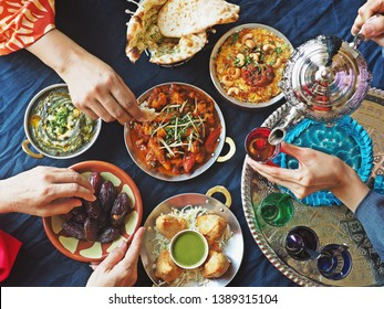 Ramadan iftar meal theme people eating variety foods together on dining table with large dates (Medjool), Samosas, Aloo Gobi, Chicken Biryani, Moroccan tea set, Palak Paneer and Naan bread. (top view)