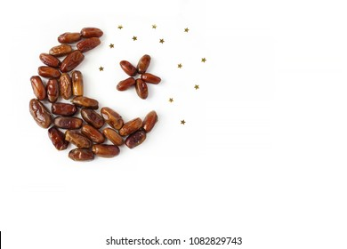 Ramadan, iftar table composition. Dried date fruit arranged in moon and star shape, golden confetti on white background. Party decoration. Food pattern. Empty space. Flat lay, top view.