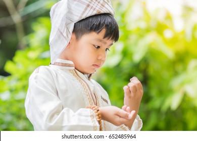 Ramadan : Islamic zakat or sadaka, adult giving money to child.Boy asian.Donate to Charity for Children.