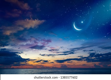 Ramadan Kareem background with crescent, stars and glowing clouds above serene sea.  Elements of this image furnished by NASA