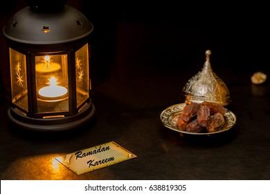 Ramadan kareem card with lantern and dates in darkness