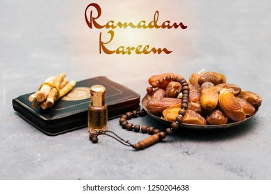 Ramadan kareem concept with  dates and holy book of muslims and rosary, siwak, perfume on wooden gray background