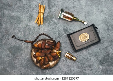 Ramadan kareem concept with  dates and holy book of muslims and rosary, siwak, perfume, candle on black background