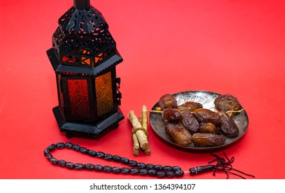 Ramadan kareem concept with  dates and lanterns and rosary, siwak on red