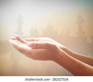 Ramadan kareem concept: Muslim prayer open empty hands with palms up over blurred mosque on sunset background