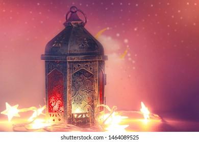 Ramadan Kareem. Decorative Arabic lantern with a burning candle. Festive greeting card, invitation to the Muslim holy holiday.