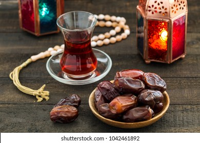 Ramadan Kareem Festive, close up of dates on wooden plate and rosary with oriental Lantern lamps and cup of black tea on wood background. Islamic Holy Month Greeting Card