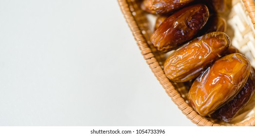 Ramadan kareem food concept with premium Dried date in a wooden basket on white background.