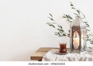 Ramadan Kareem greeting card, invitation. Silver lantern with burning candle. Turkish tea in glass on saucer. Green olive tree branches on old wooden table background. Muslim Iftar dinner. Front view.