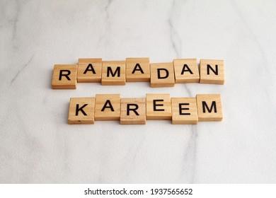 Ramadan kareem greeting letter word wooden block on marbel white background