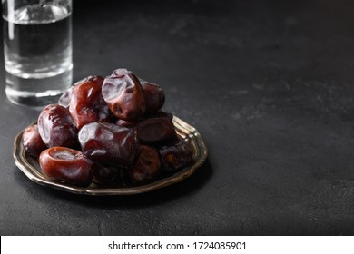 Ramadan Kareem. Iftar starts with glass of water and dates. Close up. Space for text.