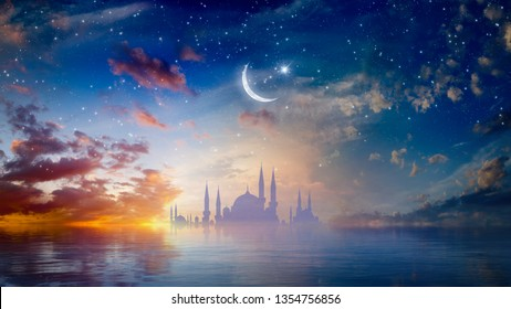 Ramadan Kareem religious background with mosque silhouettes reflected in serene sea, rising crescent and stars. Elements of this image furnished by NASA. Mixed media image.