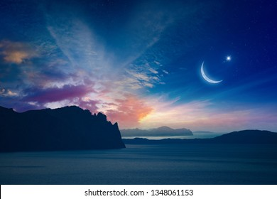 Ramadan Kareem religious background with rising crescent and stars above dark mountains and serene sea. Elements of this image furnished by NASA