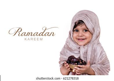 Ramadan kareem. Two year old muslim baby girl holding bowl of dates fruit.