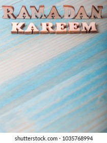 'Ramadan Kareem' words the Islamic fasting month of Ramadhan greetings meaning 'Generous Ramadan' on blue wooden table top