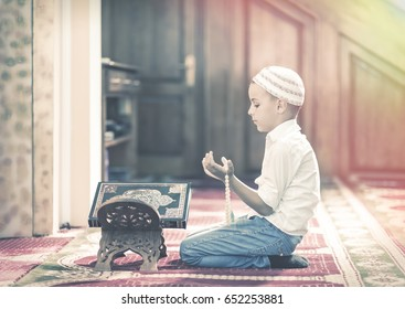 Ramadan Kareem,beautiful boy Muslim is praying in mosque,Peace and love in the holy month of Ramadan