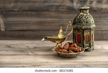 Ramadan lamp and dates on wooden background. Festive still life with oriental lantern